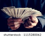 closeup of hands holding cash | Shutterstock . vector #1115280062