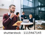 young businessman holding a... | Shutterstock . vector #1115467145
