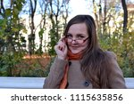 a girl in glasses smiles for a... | Shutterstock . vector #1115635856