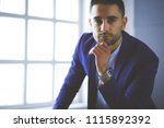 young businessman sitting... | Shutterstock . vector #1115892392