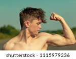 Young adult male flexing his bicep muscles shirtless on a warm summer's day - stock photo
