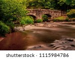Long exposure of a river flowing under a bridge in Dartmoor National Park - stock photo