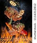 tasty beef steaks flying above... | Shutterstock . vector #1116312812