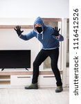 Small photo of Man burglar stealing tv set from house