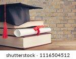 graduation black hat on desk | Shutterstock . vector #1116504512