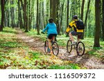 couple riding bicycle in forest ... | Shutterstock . vector #1116509372