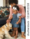 Stock photo african american little girl and her mom playing with thier dog 1116912218