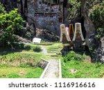 Small photo of Tana Toraja - Sulawesi (Indonesia) October 2017 Stone Carved Burial Site with Tau Tau