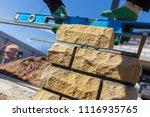 man builds a brick wall at a... | Shutterstock . vector #1116935765
