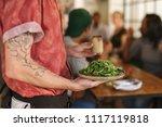 closeup of a waiter serving a... | Shutterstock . vector #1117119818