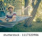 young man sitting in hammock...   Shutterstock . vector #1117320986
