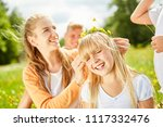 mother decorates hair of her... | Shutterstock . vector #1117332476