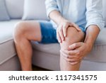 Small photo of Man suffering from knee pain sitting sofa. A mature man massaging his painful knee. Man suffering from knee pain at home, closeup. Pain knee