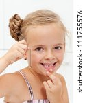 Happy little girl with her first missing milk tooth on a string - stock photo