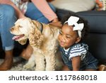 Stock photo african american little girl and her mom playing with thier dog 1117868018