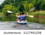 people kayaking on river at...