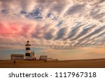 Small photo of Port Elizabeth, South Africa - October 10, 2015: unidentified tourists stroll on the beach at the landmark Cape Recife Lighthouse image with copy space in landscape format