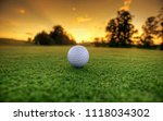 Small photo of Golf ball on tee ready to be shot on the green golf course on sunset. Golf is a club and ball sport in which players use various clubs to hit balls into a series of holes on a course in few strokes.