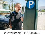 a man pays for parking using a... | Shutterstock . vector #1118103332