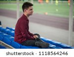 Small photo of Young lame man sitting in the stadium