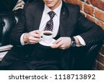 a man in a suit with a cup of... | Shutterstock . vector #1118713892