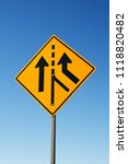 Small photo of Traffic merge sign and blue sky.
