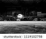 Stock photo black and white photography of aircraft towing tractors towing aircraft airplane out from 1119102758