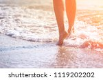Small photo of close up leg of young woman walking along wave of sea water and sand on the summer beach. Travel Concept.
