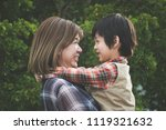 asian mother holding her son in ... | Shutterstock . vector #1119321632