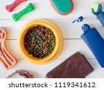 Stock photo top view of pet care concept with dry pet food in bowls and dog accessories on white table 1119341612