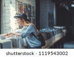 young girl browsing vinyl... | Shutterstock . vector #1119543002