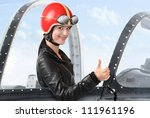 Beautiful girl in a cockpit of a vintage plane. Close up with shallow DOF. - stock photo