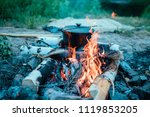 cooking in a cauldron on an... | Shutterstock . vector #1119853205