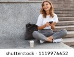Image of beautiful stylish woman sitting on street stairs with legs crossed on summer day and holding mobile phone