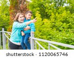 mother and son. mom shows...   Shutterstock . vector #1120065746