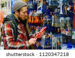 a young man chooses iron... | Shutterstock . vector #1120347218