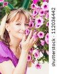 smiling mature woman and flowers | Shutterstock . vector #112036442