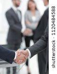 two businessmen shaking hands... | Shutterstock . vector #1120484588