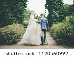 bridegroom helps walking bride... | Shutterstock . vector #1120560992