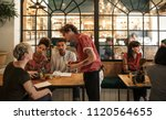 smiling young waiter taking... | Shutterstock . vector #1120564655