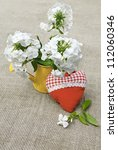 Rural still life summer bouquet from white phloxes in a yellow watering-can and tectile heart on a canvas table - stock photo