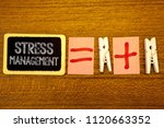 Small photo of Handwriting text Stress Management. Concept meaning Meditation Therapy Relaxation Positivity Healthcare White paper clip laid woody desk black slate some texts equal and plus mark.