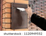 Woman Putting Letter In Mailbo...