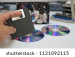 a hand with floppy disk  cd rom ... | Shutterstock . vector #1121092115