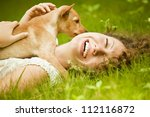 Stock photo happy woman lying on the grass with her dog in the park 112116872