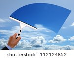 Window cleaner using a squeegee to clear the blue sky above - stock photo