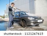 young man in sunglasses washing ... | Shutterstock . vector #1121267615