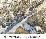snowy road with a moving car in ... | Shutterstock . vector #1121300852