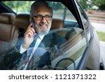 happy business man in car.... | Shutterstock . vector #1121371322