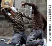 Small photo of AURILLAC, FRANCE - AUGUST 24: two masked dancers are kneeling, face to face, as part of the Aurillac International Street Theater Festival, Company Idem,on august 24, 2012, in Aurillac,France.